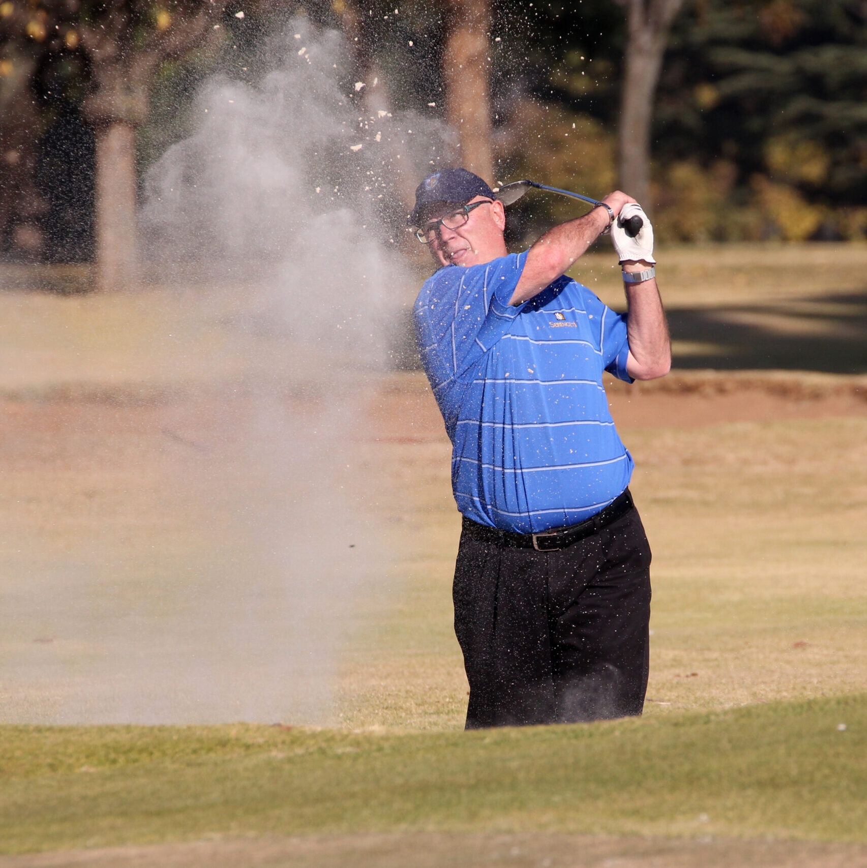 man hitting golf ball out of sand trap