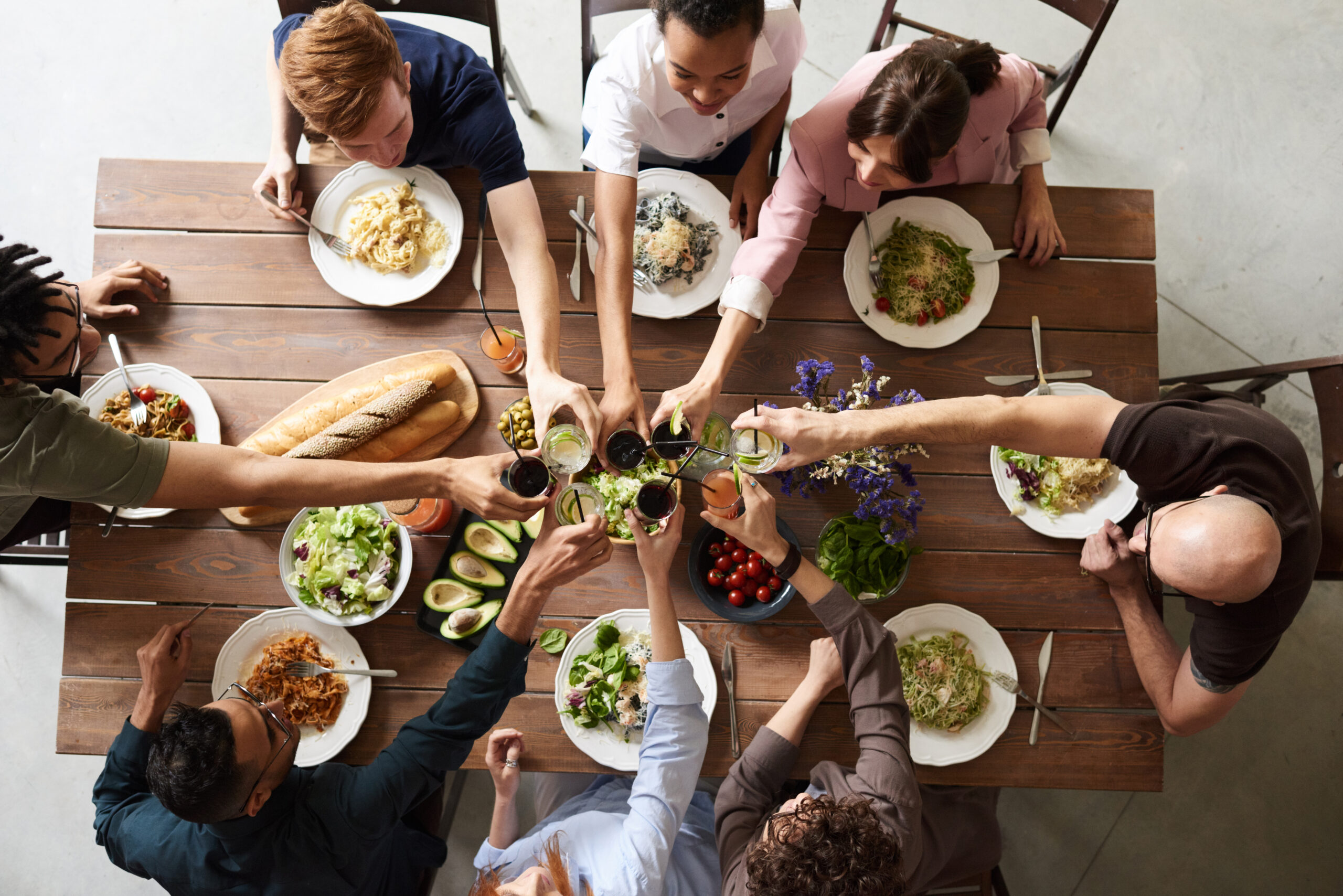 Overhead photo of group of people eating and toasting